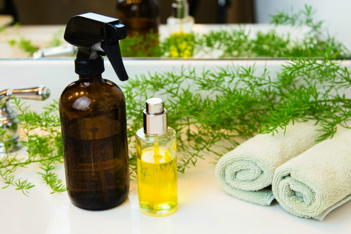 Amber and clear glass spray bottles. Rolled green towels in a spa setting. Green plant decor in background. Bathroom white countertop.