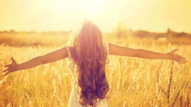 Dark haired girl with open arms looking at the sun