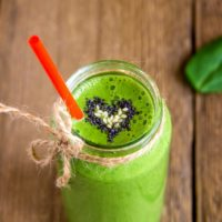 Green smoothie with heart of seeds in jar over rustic wooden background