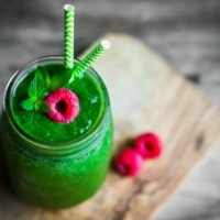 Green smoothie ina mason jar with a raspberry on top on rustic wooden background