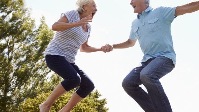 Older couple jumping on trampoline