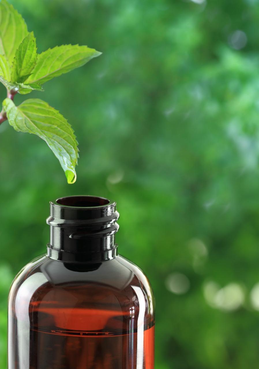 Drop falling of leaf in an amber essential oil bottle