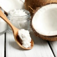 Coconut with jars of coconut oil on wooden background