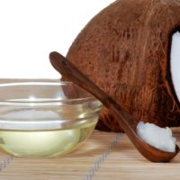 Open coconut, coconut oil in a bowl with a spoon