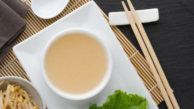 Thai dressing in a white bowl with bamboo background and chopsticks