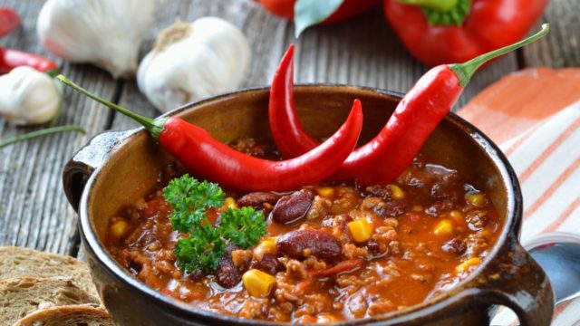 Bowl of chili with red chili peppers on top