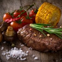 Cooked steak with tomatoes, corn, and mushroom on a rustic wood background