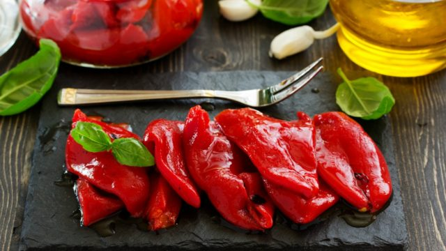 Roasted red peppers on a dark background with garlic and olive oil on the side