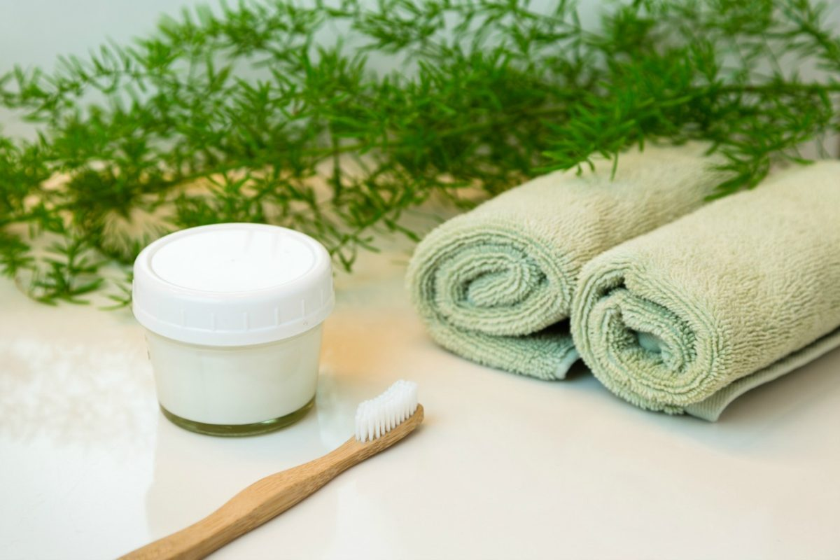Homemade toothpaste in mason jar and bamboo toothbrush. Rolled green towels in a spa setting.