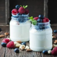 Two mason jars with milk and topped with fruit